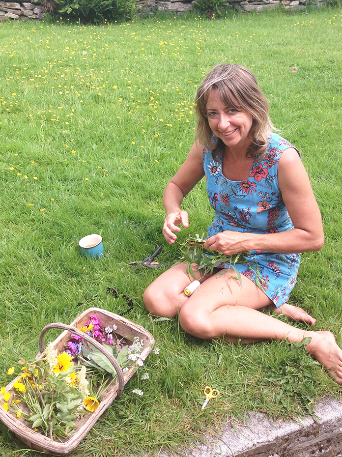 Gardener in sunshine making flower crown with basket