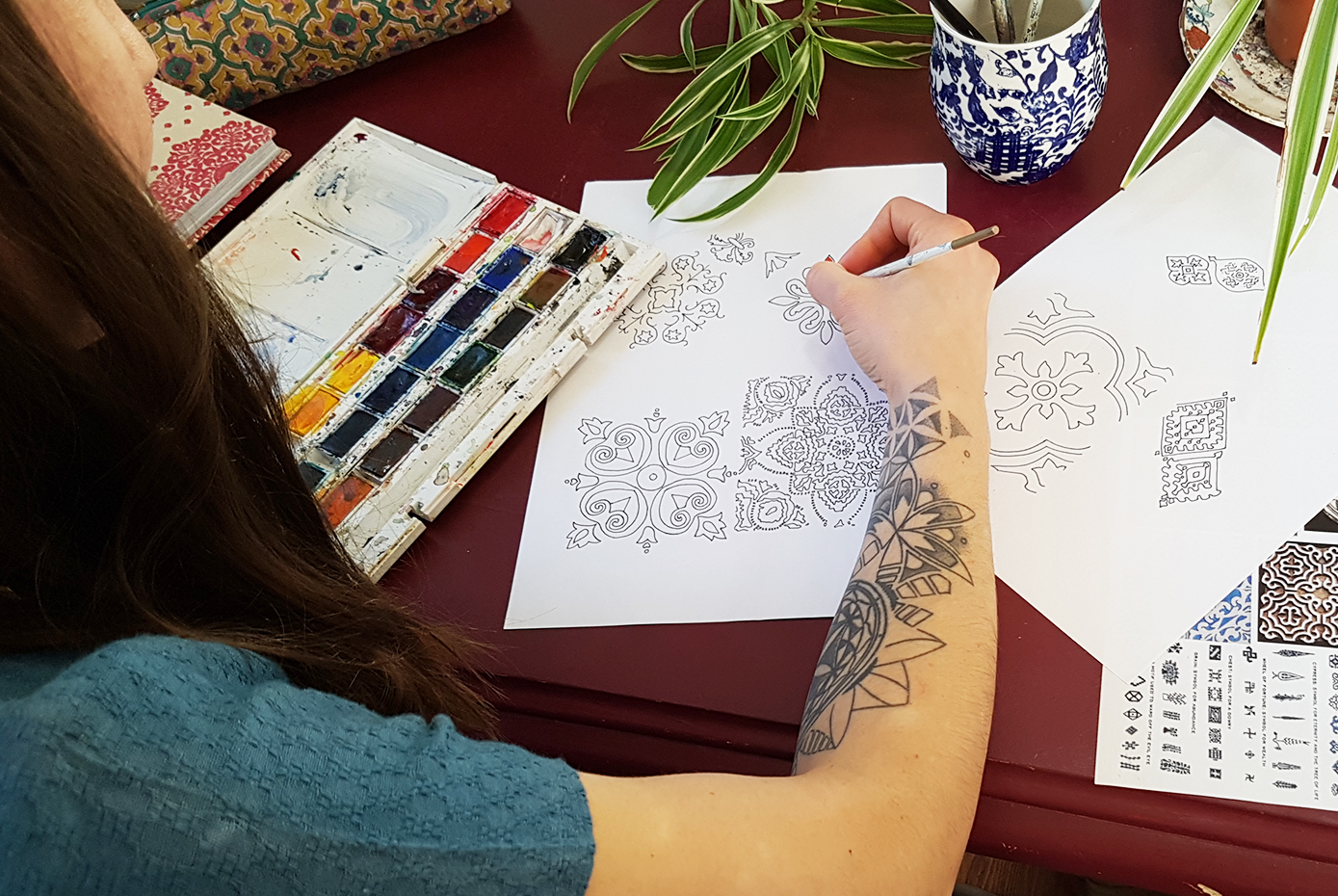 woman with tattooed arm paining patterns with watercolour paints