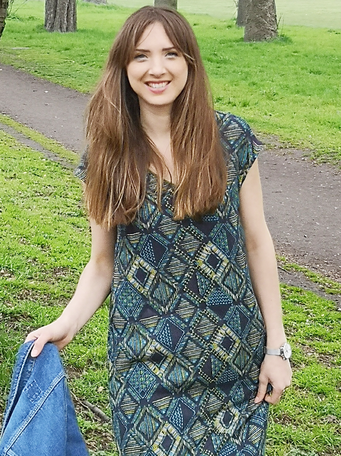 girl wearing maxi dress with denim jacket in park