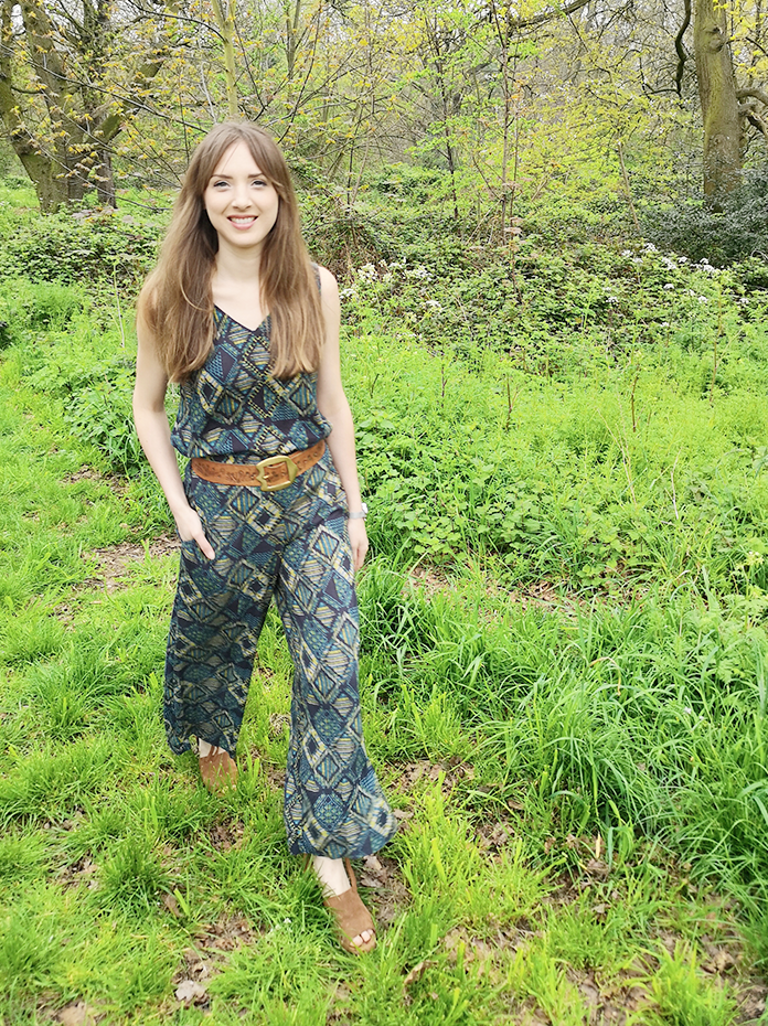 Girl walking in park wearing printed vest and wide leg trousers
